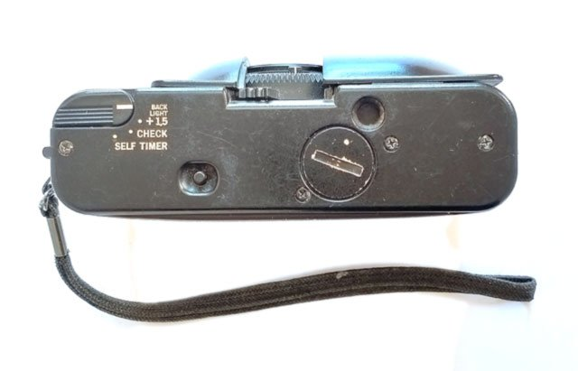 The bottom plate with the small lever to set back-light compensation, battery check, and self timer.